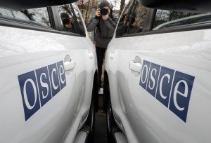 A journalist takes picture during a handover ceremony of armoured vehicles donated by Britain to the OSCE Special Monitoring Mission to Ukraine, in Kiev