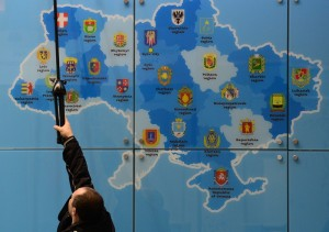 A worker adjusts lights above a tourist map of the Ukraine at the Ukraine stand of the ITB International Travel Trade Fair in Berlin March 4, 2014. The ITB open from March 5 to 9, 2014. TOPSHOTS/AFP PHOTO / JOHN MACDOUGALL