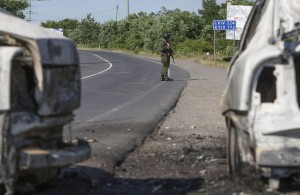 An interior ministry serviceman stands next to burnt cars following a shoot-out in Mukacheve, Ukraine, July 11, 2015. Ukraine's President Petro Poroshenko has instructed law enforcement agencies to disarm and detain those who staged the shoot-out in the town of Mukacheve, Zakarpattia region, which left several people wounded and some reportedly killed, local media reported. REUTERS/Stringer