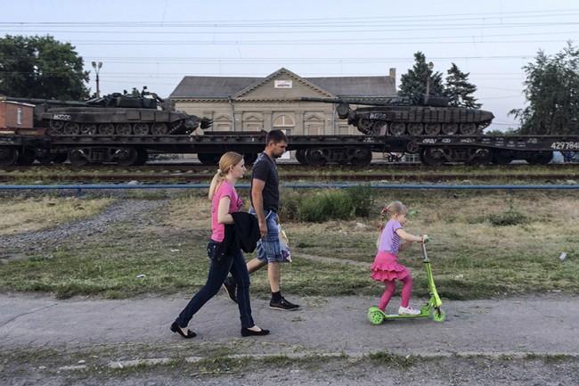 Tanks are seen on a freight train shortly after its arrival at a railway station, with people walking in the foreground, in the Russian southern town of Matveev Kurgan, near the Russian-Ukrainian border in Rostov region, Russia, May 26, 2015. Picture taken with a mobile phone. REUTERS/Maria Tsvetkova - RTX1EN0H