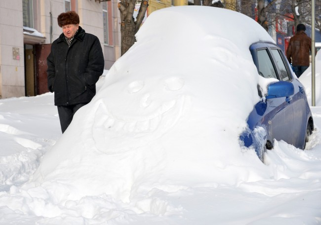 A man walks past a car covered with snow after a heavy snow storm hit the Ukrainian capital of Kiev on March 24, 2013. Kiev administration declared a state of emergency in the city and announced that residents could take the day off tomorrow following three days of heavy snowfalls.  AFP PHOTO/SERGEI SUPINSKY        (Photo credit should read SERGEI SUPINSKY/AFP/Getty Images)