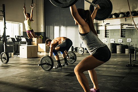 People training with barbels and gymnasium rings