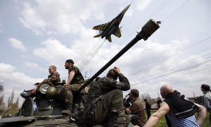 A fighter jet flies above Ukrainian soldiers in Kramatorsk